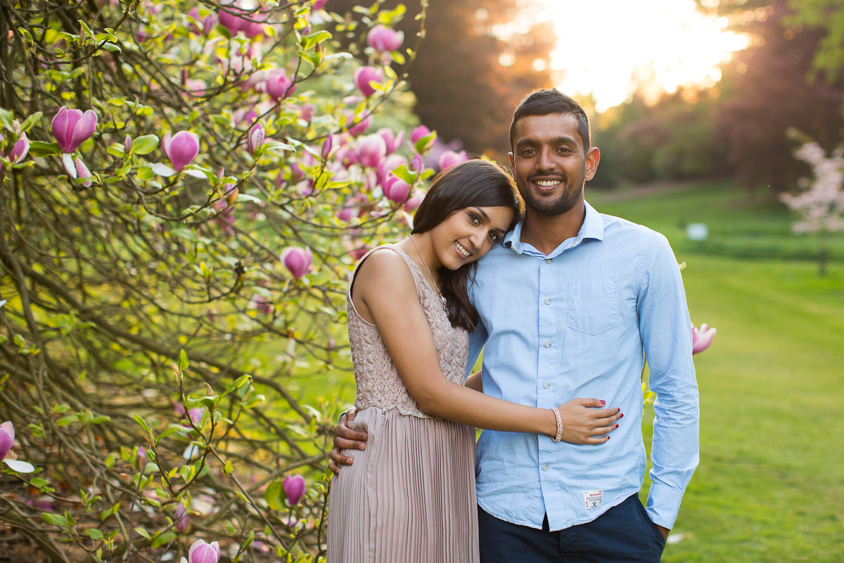 happy couple posing for their engagement photos in between magnolia blossom