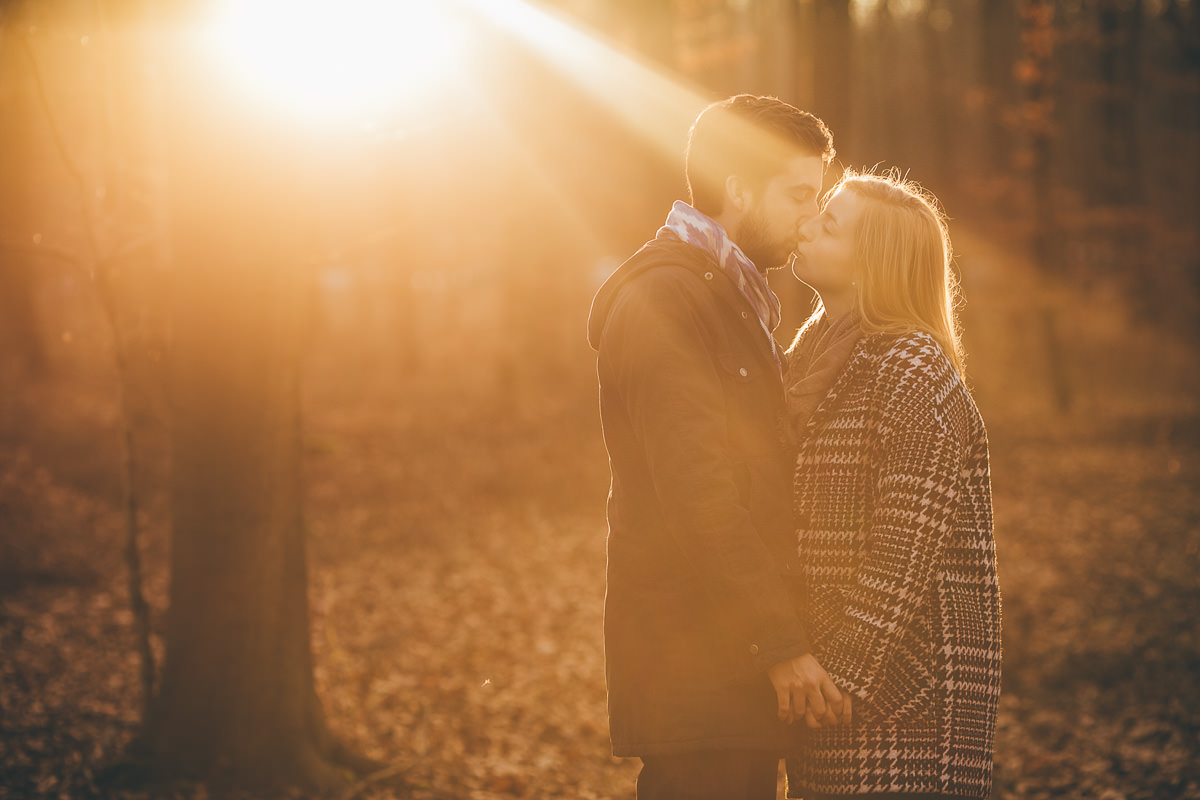 newly engaged couple kissing during a golden hour