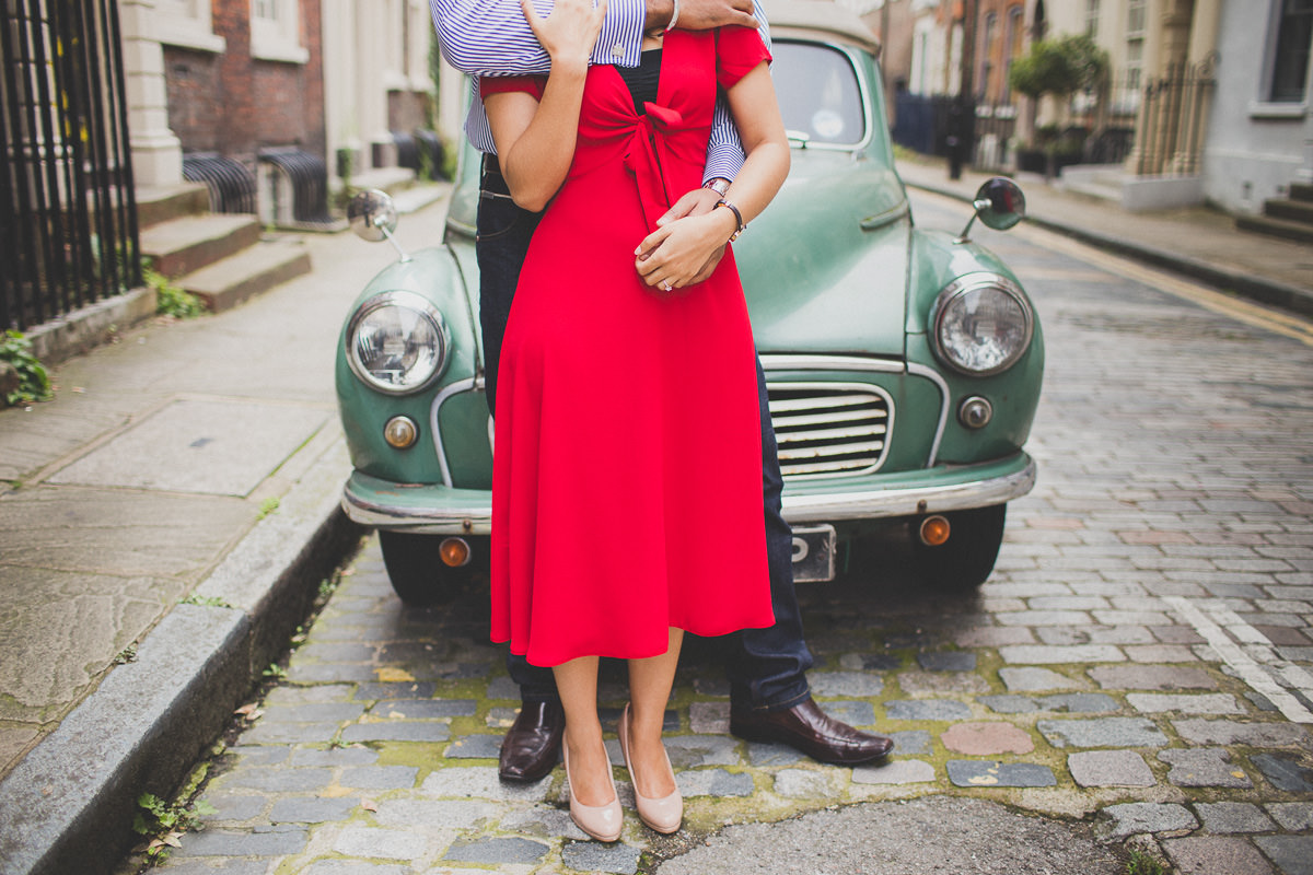 creative engagement photo shoot with a lady in a red dress and a vintage car in London