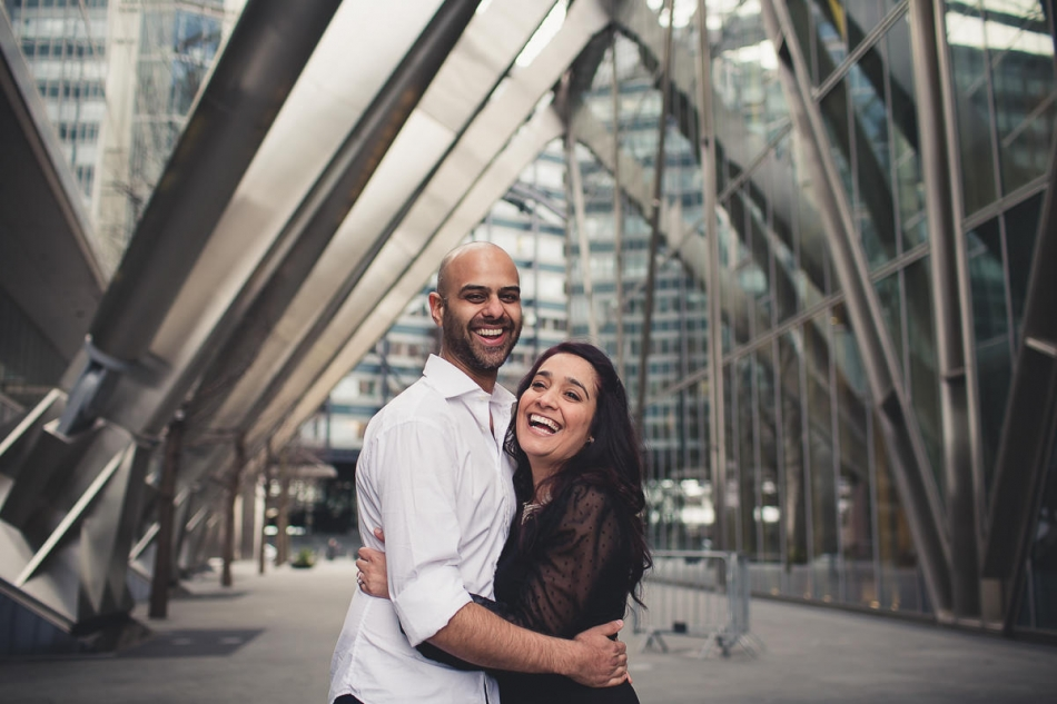 happy couple laughing and smiling while posing for their London engagement photography