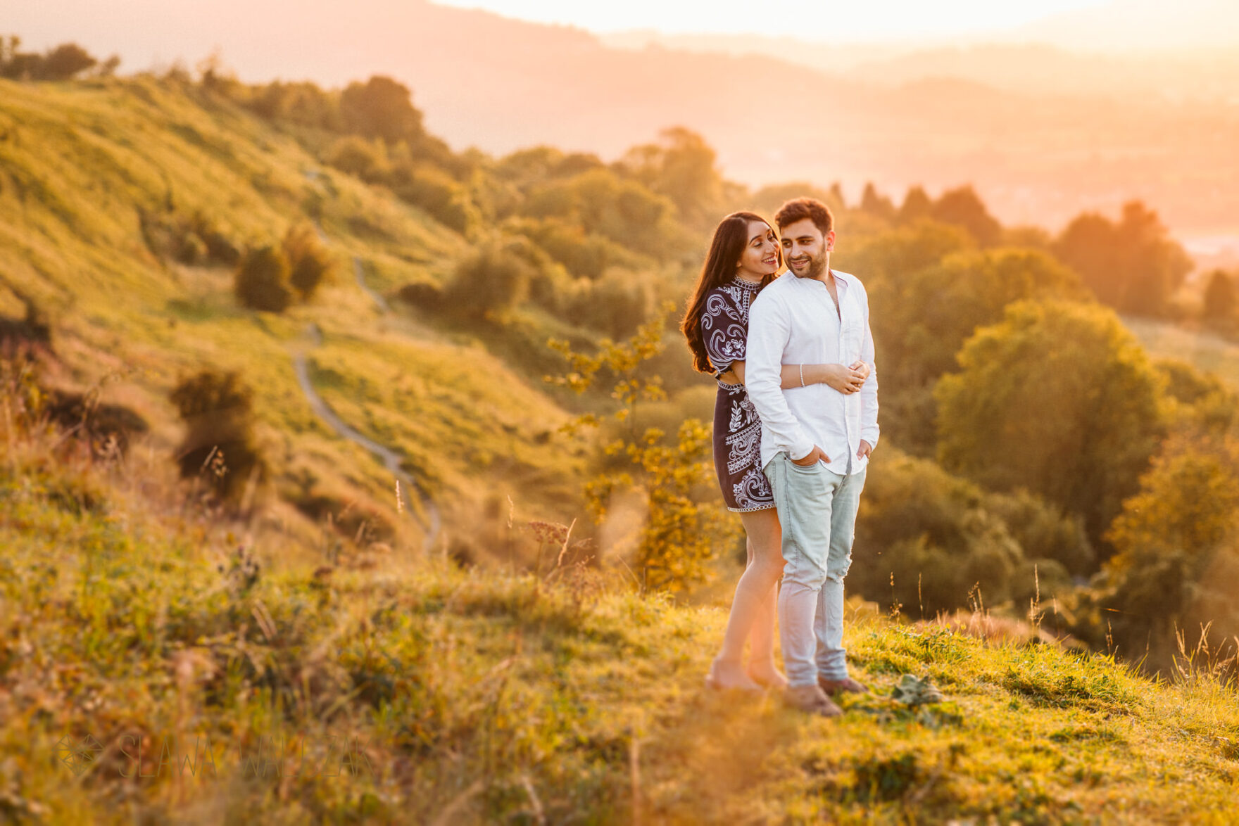 asian couple on top of a hill posing for their engagement photos during golden hour