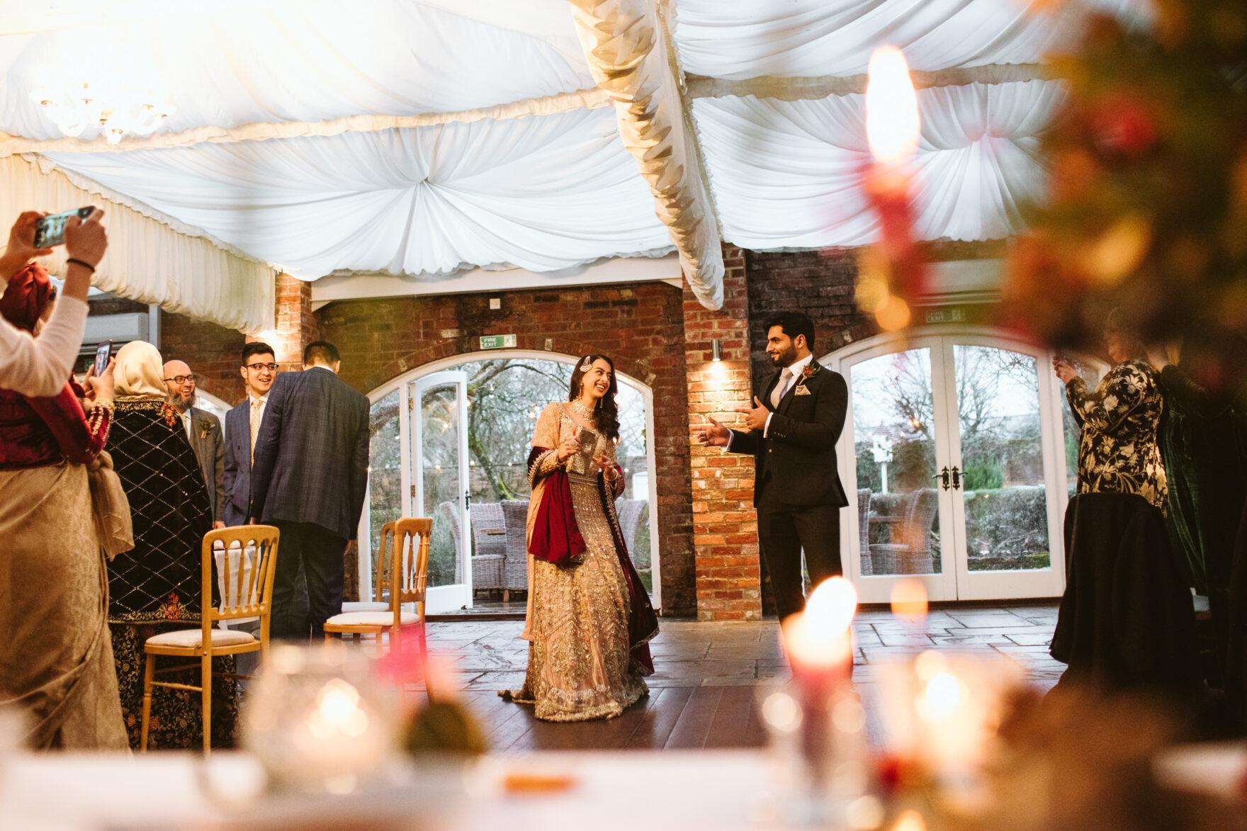 Muslim bride and groom entering her wedding reception