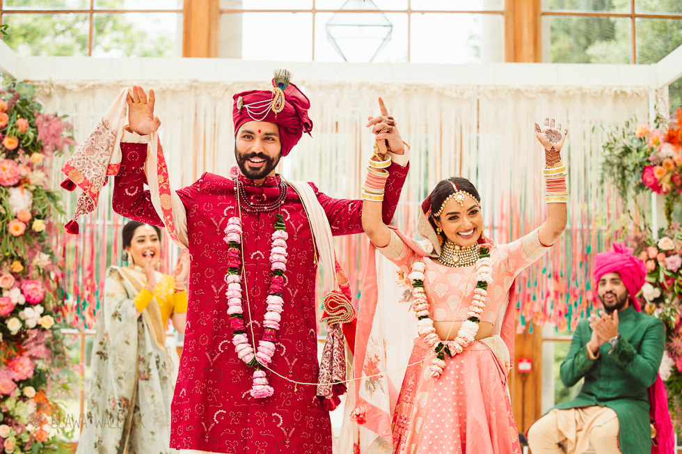 Hindu Bride and Groom Cheering while posing to an Asian London Wedding Photographer at Kew Gardens