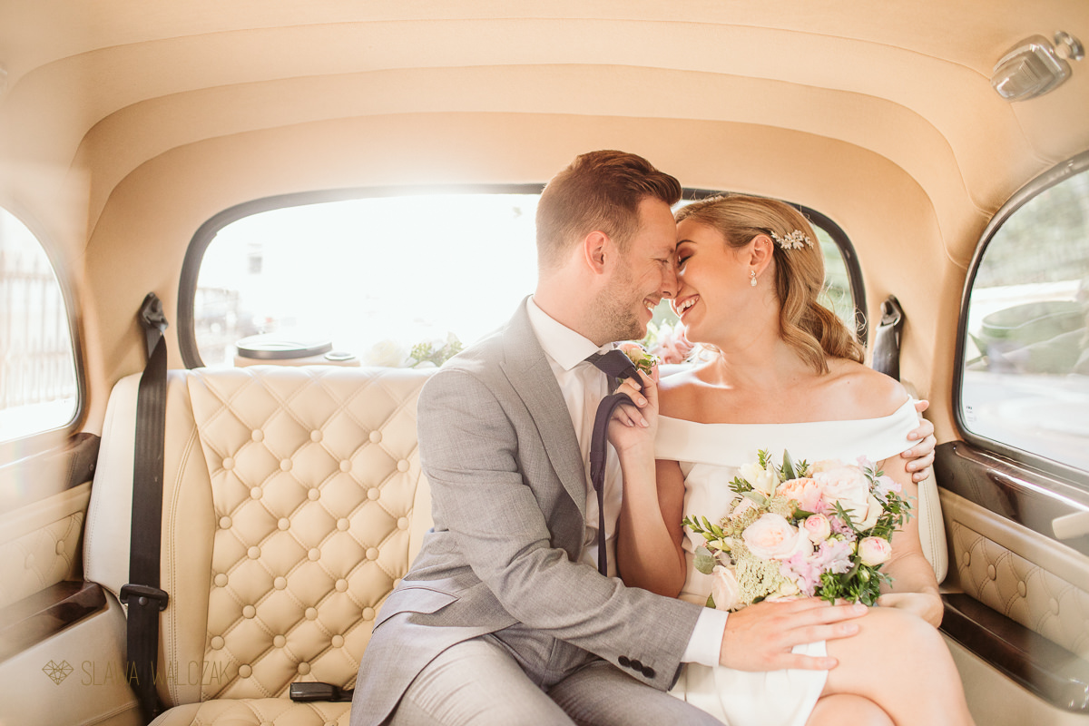 Newlywed couple kissing in the wedding car after their London wedding